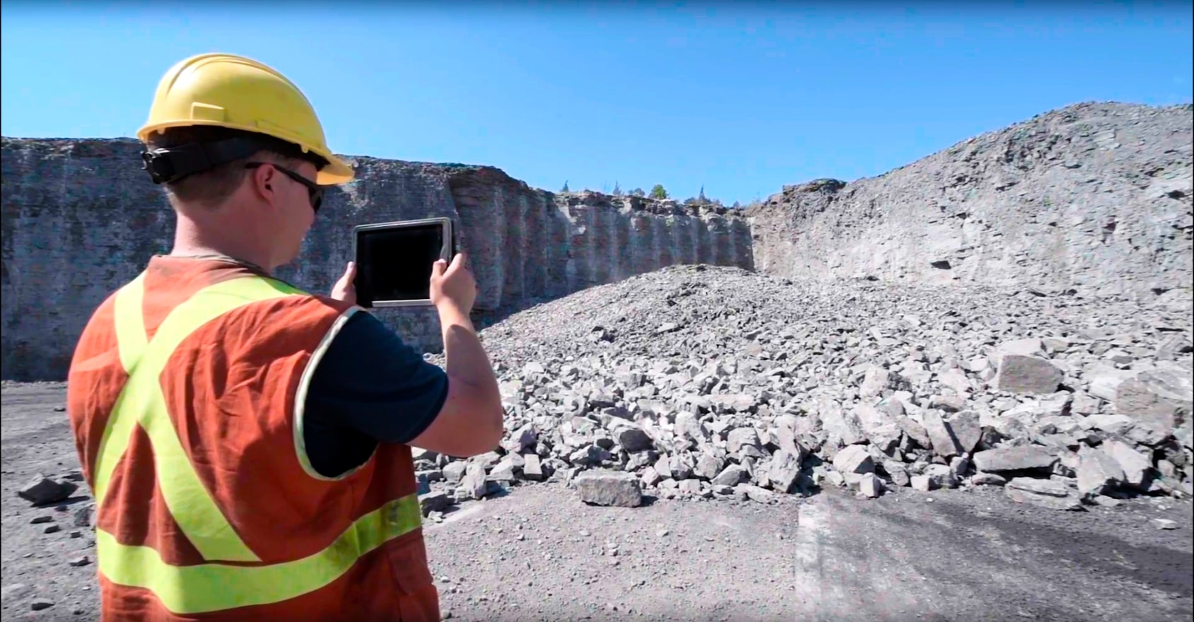Waist up shot of a worker wearing a safety vest and a hard hat taking a photo of a rock pile using an ipad with Wipfrag to see fragmentation analysis.