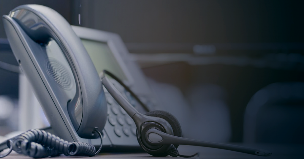 Image of a landline phone next to a headset used for support calls.
