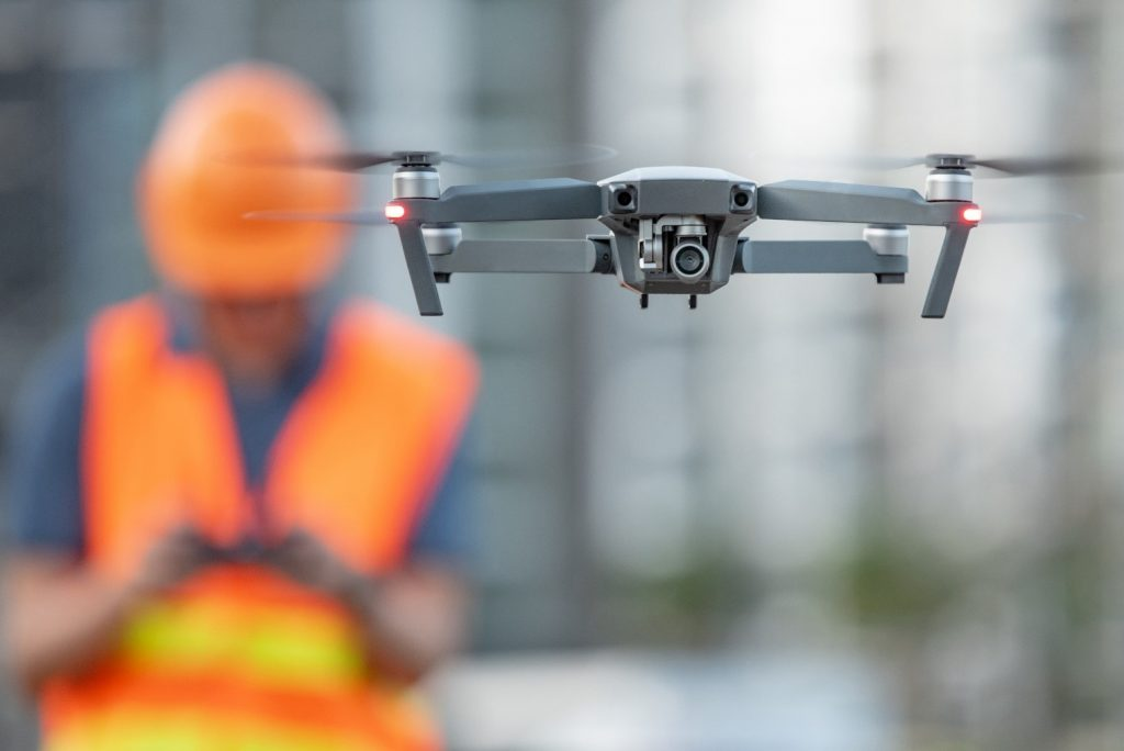 A worker in hi vis standing behind controlling a drone.