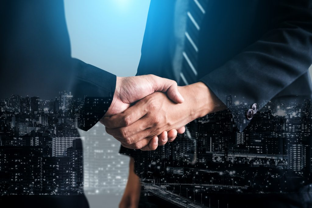 Double exposure image of business concept, people handshake on city office building background.